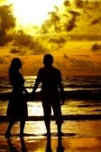2308333-view-of-young-couple-walking-along-the-shore-during-sunset